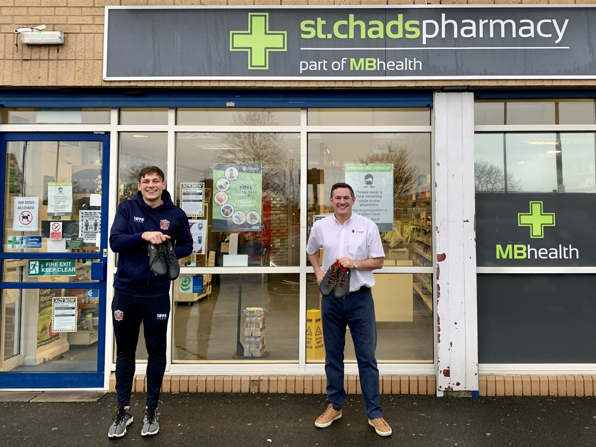 Liam Bent (left) and Martin Molyneux, of St Chad's pharmacy, showing off the boots outside the Lime Green Parade store.